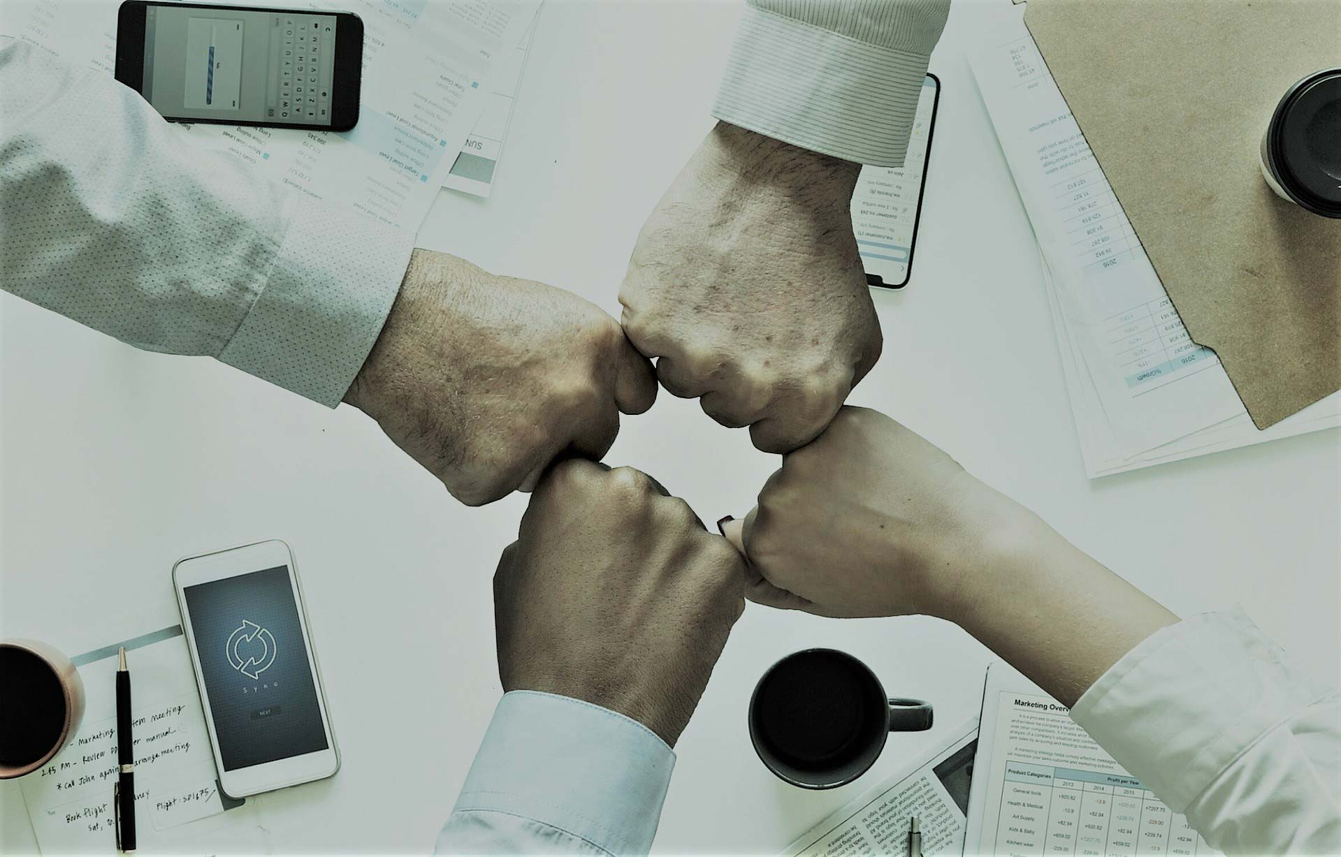 Four fists of team members meeting in the middle, representing collaboration in a translation business