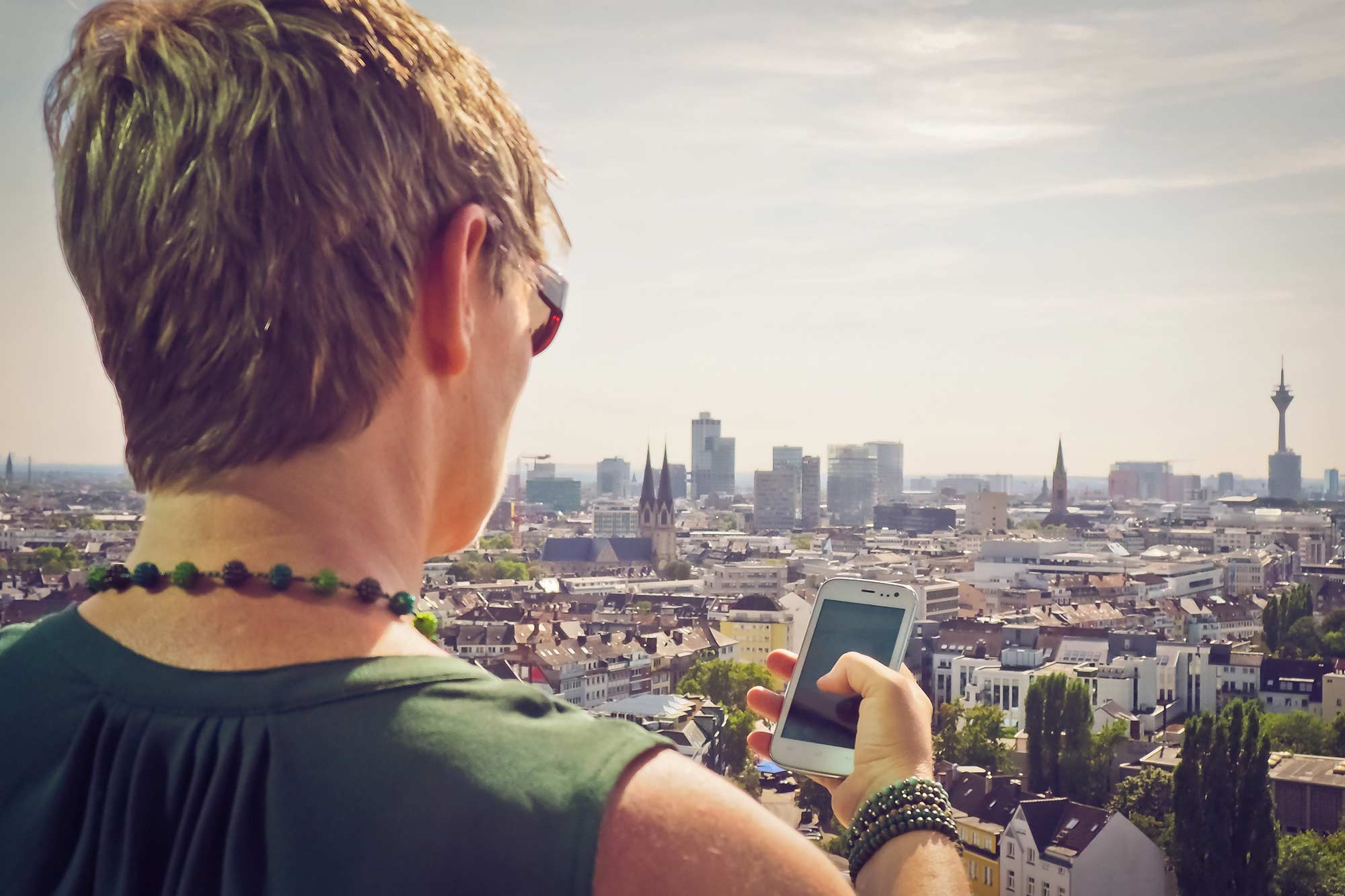 Translator Claudia Dalberg on the phone with a customer and a view of Dusseldorf